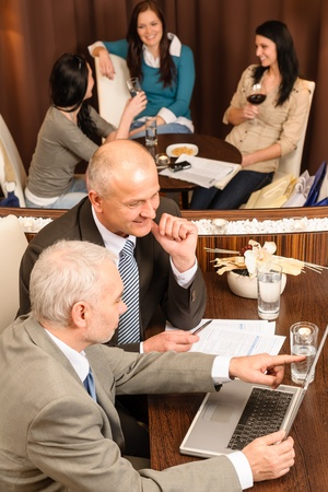 Two mature businessmen having coffee break at the restaurant photo