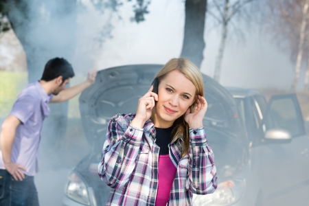emergency call: Car breakdown woman call for help road assistance smoking engine Stock Photo