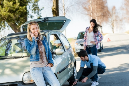 roadside assistance: Broken wheel man changing tire help two female friends