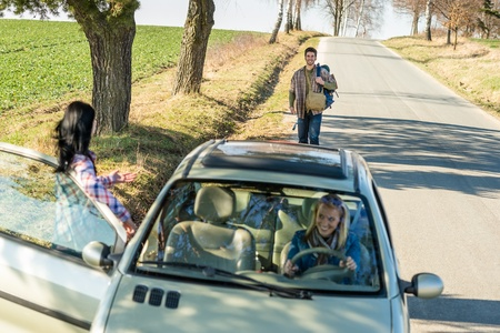 hitch hiker: Young man road trip girl friends offer lift with car