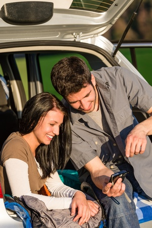 Happy couple in camping car looking at camera pictures sunset photo