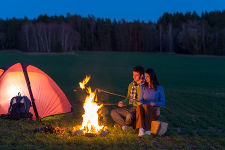 campfires: Camping night couple cook by campfire backpack in romantic countryside Stock Photo