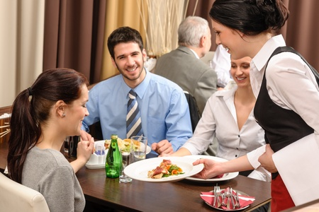 serving: Business people enjoy lunch at the restaurant waitress serving woman Stock Photo