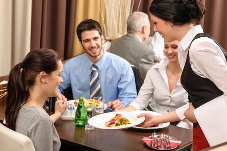 La gente de negocios disfrutar de un almuerzo a la camarera restaurante que sirve una mujer Foto de archivo