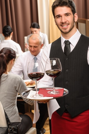 Young waiter hold red wine business lunch at professional restaurant Stock Photo - 13125683