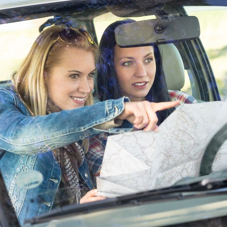 Lost with map two young friends in car enjoy road trip Stock Photo - 13152470