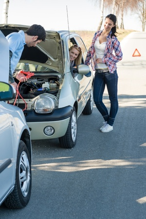 Starter cables man help to repair car two female friends Stock Photo - 13152505