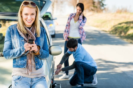 roadside assistance: Puncture wheel man changing tire help two female friends Stock Photo
