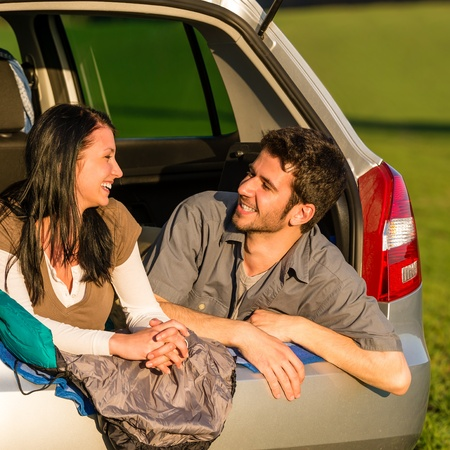 Camping young couple hugging together in car summer sunset photo