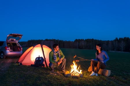 campfires: Tent camping car couple romantic sitting by bonfire night countryside