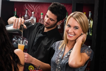 Young happy girl at cocktail bar bartender mixing drink photo