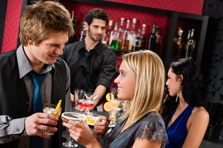 flirting: Cocktail bar young happy couple friends enjoy drinks