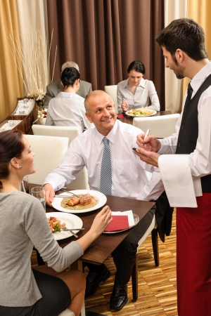 serving: Business people served by waiter enjoy lunch at the restaurant Stock Photo