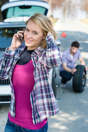 Car trouble woman calling road assistance man change broken wheel Stock Photo - 13165937