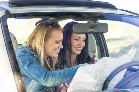 Lost with map two young friends in car enjoy road trip photo