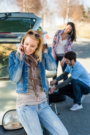 Broken wheel man changing tire help two female friends Stock Photo - 13165931