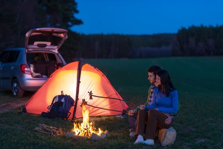 Tent camping car couple romantic sitting by bonfire night countryside photo