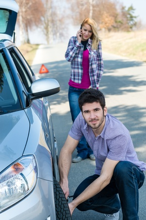 Car wheel defect man change puncture tire woman calling assistance Stock Photo - 13258479