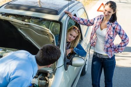 broken car: Car failure man help two female friends repair motor