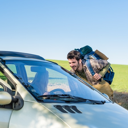 hitch hiker: Hitch-hiking getting lift young woman in car road trip Stock Photo