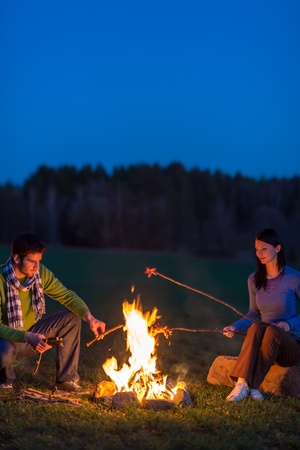 Young couple cook by campfire romantic night countryside