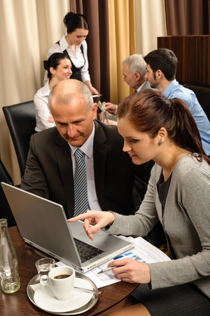 Business people discussion woman point laptop at restaurant conference room photo