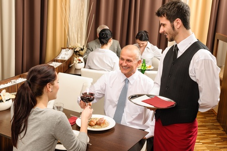 Business lunch executive people toast with red wine young waiter serve photo