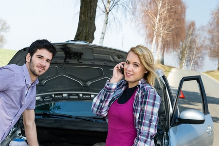 Car breakdown couple calling for road assistance repair motor defect photo