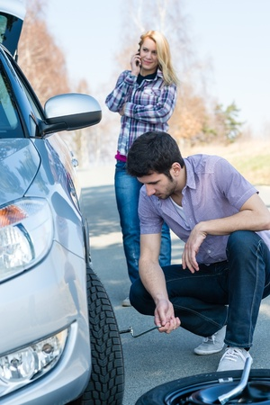 Car wheel defect man change puncture tire woman calling assistance photo