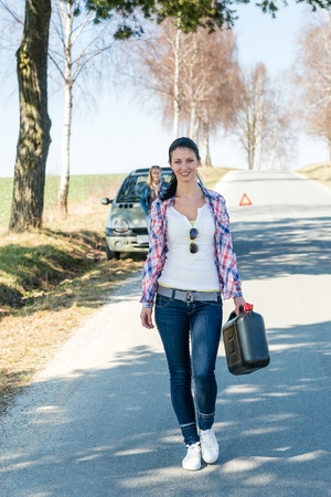 re fuel: Running out of gas young woman walking for petrol can Stock Photo