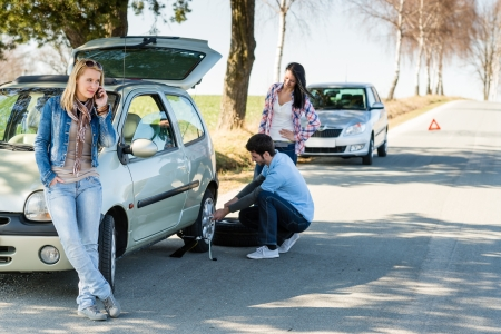 changing: Broken wheel man changing tire help two female friends