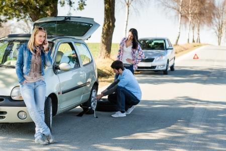tire service: Broken wheel man changing tire help two female friends