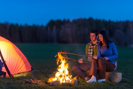 bonfire night: Camping night couple cook by campfire backpack in romantic countryside Stock Photo