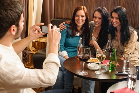 Young friends at the bar man take picture of three women photo