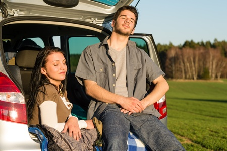 Happy camping couple lying inside car enjoy summer sunset countryside photo