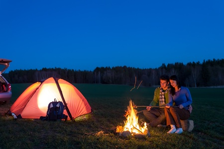 camping: Tent camping car couple romantic sitting by bonfire night countryside