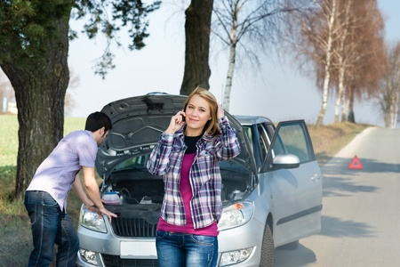 Car breakdown couple calling for road assistance man look engine photo