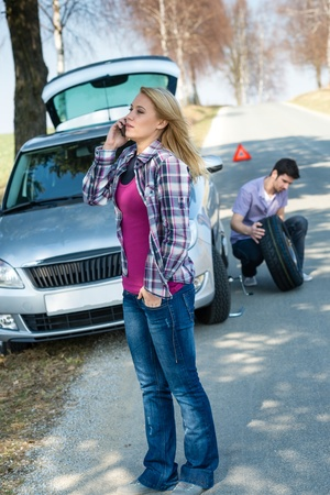 Car trouble woman calling road assistance man change broken wheel photo