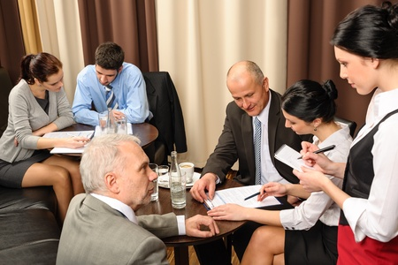 Business people having a company meeting at restaurant waitress ordering photo