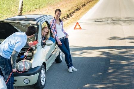 Car failure man help two female friends repair engine photo