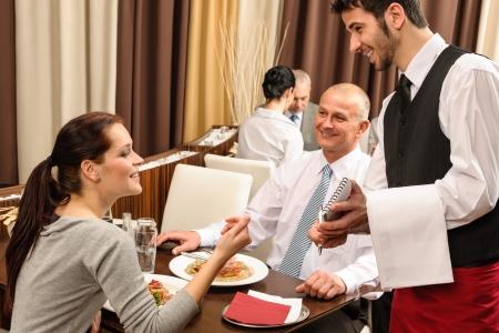 웨이터에 의해 제공 비즈니스 사람들이 레스토랑에서 점심 식사를 즐길 수