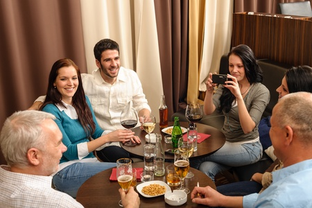 social gathering: Business people having drink after work taking picture of themselves Stock Photo