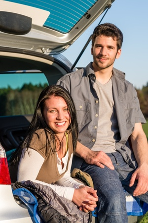 Camping young couple smiling together in car summer sunset photo