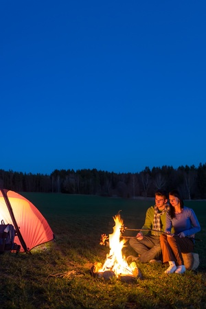 Camping night couple cook by campfire backpack in romantic countryside photo