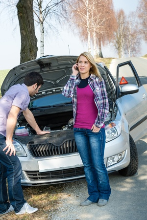 defect: Car breakdown couple calling for road assistance repair motor defect Stock Photo