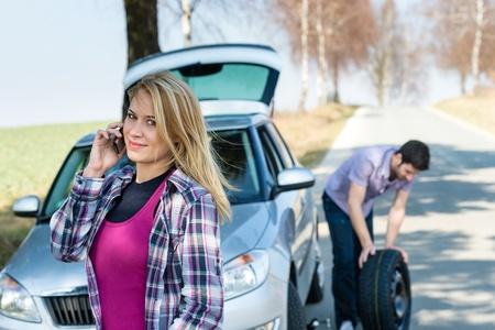flat tyre: Car wheel defect man change puncture tire woman calling assistance