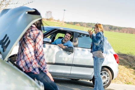 damaged: Car troubles two woman friends asking help young man Stock Photo