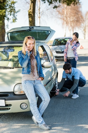 Broken wheel man changing tire help two female friends photo