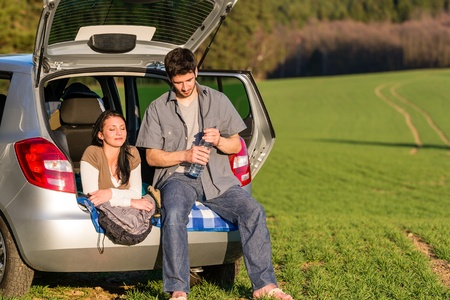 Happy camping couple lying inside car summer sunset countryside photo