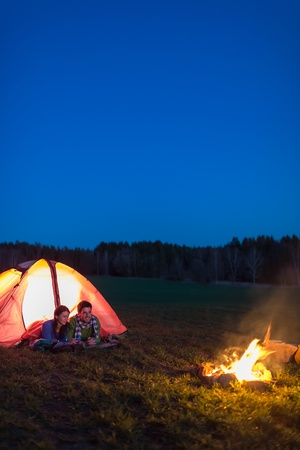 Romantic camping night couple lying in front tent by campfire photo